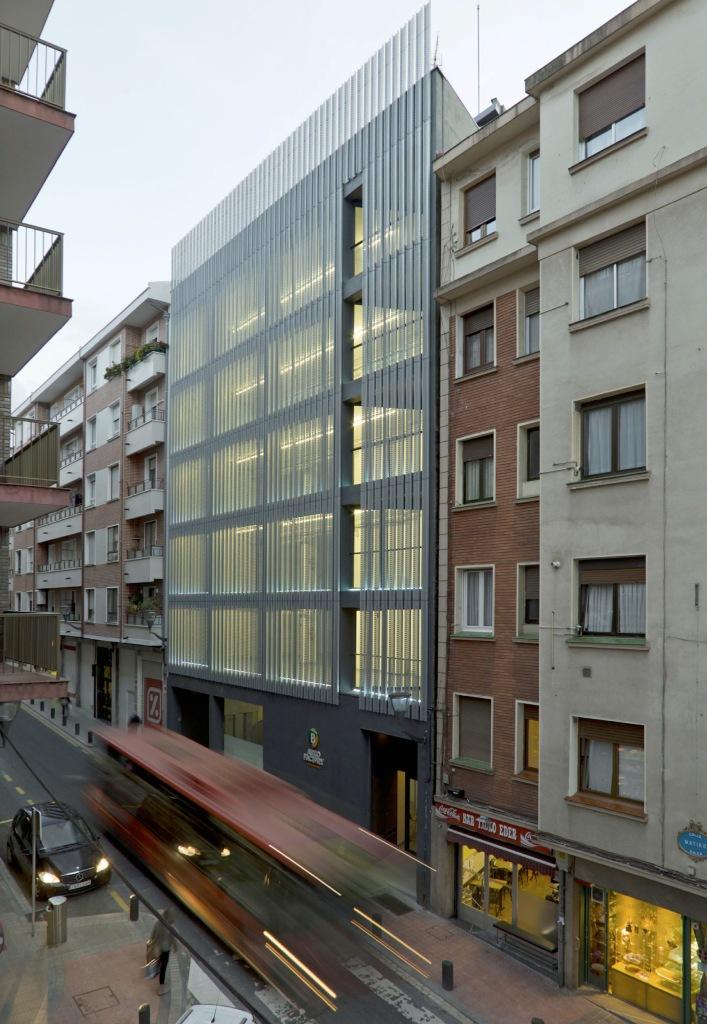 """AUZO FACTORY IRAZABAL-MATIKO, UN ESPACIO PARA IMPULSAR LA ECONOMÍA URBANA Y EL DESARROLLO SOCIAL El centro, que ocupa un inmueble de más de 1.400 m2, albergará proyectos empresariales, intensivos en conocimiento y tecnología, y será un referente para el movimiento asociativo. Bilbao, a 31 de marzo de 2014. Los barrios cobran protagonismo en Bilbao. La economía urbana, vinculada al conocimiento, la creatividad y la tecnología, busca nuevos espacios de oportunidad para instalarse y desarrollar iniciativas empresariales, que contribuyan a generar crecimiento, dinamismo y bienestar. Es el momento de los barrios. Tienen alquileres más asequibles, muchos son accesibles a pie, están bien comunicados a través de una completa red de transporte sostenible y sus habitantes son conscientes del valor y el futuro que puede aportar a sus barrios la """"llegada"""" de jóvenes emprendedores, con ideas y talento. Auzo Factory, concepto urbano Auzo Factory es un proyecto, impulsado por el Ayuntamiento de Bilbao, pensado por y para el municipio. Su objetivo es la creación de actividad económica en los barrios de la ciudad, recuperando para ello edificios en desuso o infrautilizados, que se transforman en fábricas de creatividad y participación para albergar propuestas empresariales y ser, al mismo tiempo, un referente de la convivencia y el movimiento vecinal. El concepto Auzo Factory responde, de hecho, al compromiso del Ayuntamiento de Bilbao, recogido en el eje 6 del Plan de Gobierno 2011-2015, que apuesta por favorecer el dinamismo económico, comercial y social de los barrios de la ciudad. Irazabal-Matiko, un primer paso Irazabal-Matiko es el primer Auzo Factory, que abre sus puertas en Bilbao. Ubicado en un edificio sin uso desde su construcción en 1960, propiedad de la familia Irazabal, aspira ahora a convertirse en un modelo para construir y entender la filosofía Auzo Factory. Irazabal-Matiko tiene una razón de ser: estimular la economía urbana, fomentando la colaboración entre cluste"""